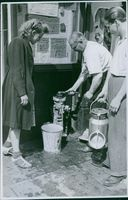 People filling water and communicating with each other. 1944