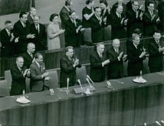 lexei Nikolayevich Kosygin standing with other people and clapping hands together. 1955