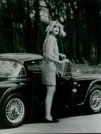 Woman standing beside car and looking at someone.
