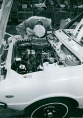 Man working on car.  Man working on a car in a car factory. Tokyo 1988.