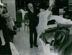 Shopkeeper helps Madame Nhu, the de facto First Lady of South Vietnam, try on some fabrics. Rome, 1963.