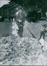 Man cleaning street with the broom and looking towards the camera.