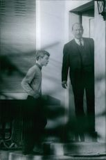 Child stepping up and entering in the house and man looking out.