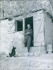 Man coming out from the hut, while a dog looking.