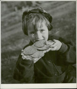 A Finnish child eating a salami in the evacuation site. 1944