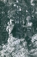 A soldier walking, pointing his finger, with a man carrying a little boy and another man behind him, in Vietnam.