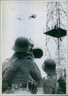 Soldier pointing his gun at plane flying in the sky, with another soldier standing beside him.