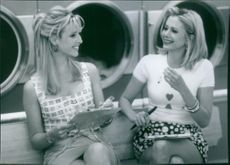 """Lisa Kudrow and Mira Sorvino sitting together and talking to each other in a scene from the movie, """"Romy and Michele's High School Reunion""""."""