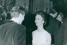 Prince Xavier and Queen Madeleine talking to each other and smiling during a party. 1969