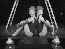 Two women sitting and smiling.