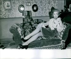 Ulla Jacobsson having a glass of drink while sitting on the couch. 1967.