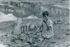 A kid from Vietnam pictured covering his nose while walking on rubbles.