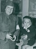 Frida Björkholm and Marion Andersson are the names of them who are in the pictue. Frida Björkholm is the lady and Marion Andersson is the little girl. They both are smiling and they also have wear fancy dress.