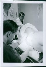A man lying-in hospital while an Epidural - catheter is fastened with by a doctor. 1971
