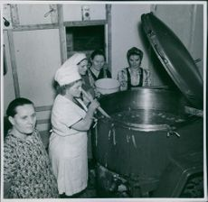A woman cooking, other women standing beside her looking and smiling.