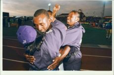 Linford Christie hugged by an unidentified person.