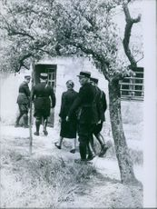 Soldiers escorting a woman towards a building.
