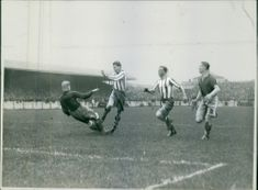 Footballers playing football match in the ground, kicking and collapsing.