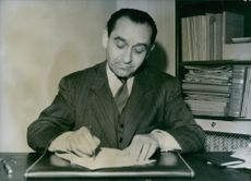 Pierre Mendes France signing on a paper.