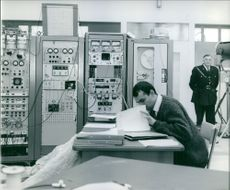 1965  A photo of a man siting and looking documents in the control room with an old man wearing uniform standing back of him.