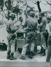 1961 Brazil. Soldiers gathered around a trolley to buy snacks.