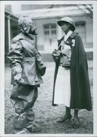 Two nurses standing and talking together, equipped with special suit.