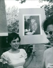 Woman holding placard of a boy, 1963.
