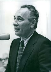 Shimon Peres speaking on a microphone.
