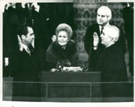President Richard Nixon takes the oath as advocated by Warren Burger. Between them Pat Nixon and in the background Senator Marlow W. Cook