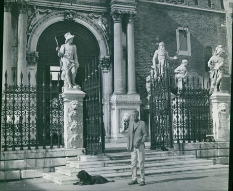 alf kjellin and his dog, standing outside the gate of a building. 1968.