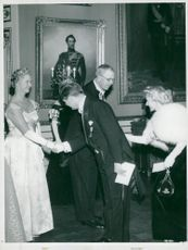 Parliamentarian Attorney Ingrid Gärde Widemar greets King Gustaf VI Adolf while a colleague to her bows for Princess Sibylla