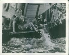 People in the boat trying to save a sinking man.