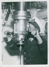 Captain on the lookout with the periscope aboard a naval submarines