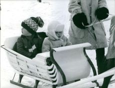 Two children riding a snow cart.