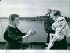 Former Prime Minister of Finland Urho Kekkonen passing a joyful moment with his grandchild who being carried by him and his wife Sylvi Uino, they are smiling