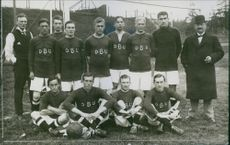 Football team standing with coach. 1913