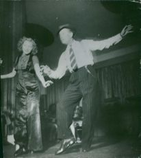Maurice Auguste Chevalier dancing with a woman.