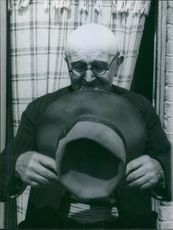 A man holding a hat. 1960
