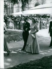 Princess Beatrix of the Netherlands walking with a man holding his arm giving public appearance to the people.