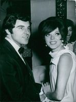 English actor and singer Anthony Newley seen with his wife actress Joan Collins, while they are looking at something with smiling face