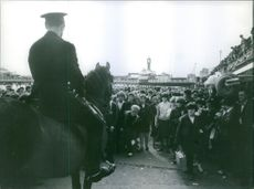 A huge number of crowd gathered to see someone special, man on horse.