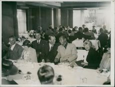 Maurice Auguste Chevalier talking to a man, in social gathering.
