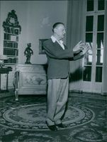 Somerset Maugham is in a room standing and demonstrating something with both hands.