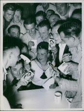 Maria Sazarina with a group of men holding her photograph, 1940.