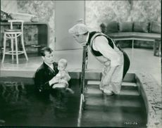 Maurice Auguste Chevalier standing in pool.
