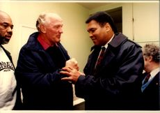 Muhammad Ali in conversation with Henry Cooper at his gym.