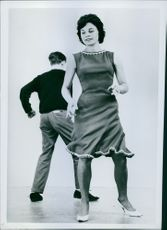A male and female model pictured dancing. 1962.