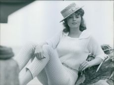 Tina Louise sitting and looking at something.