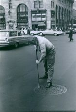 Detective Jim Gibbons posing as a street worker but seems to be having some difficulty getting the trick of lifting manhole covers down.