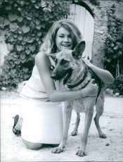Laura Ulmer is smiling beside her pet dog.